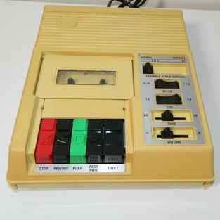 A portable four track cassette player is depicted.  Yellow in colour with control buttons.  These were common two decades ago to proivde people with vision loss access to audio recordings.